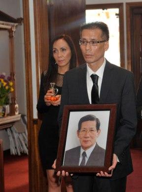 Nguyễn Sơn Vũ, con trai nhà văn Nguyễn Trường Sơn, mang di ảnh  vào nhà nguyện Trung Tâm Công Giáo. (Hình: Văn Lan/Người Việt)